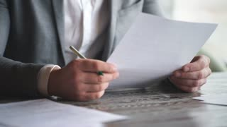stylish young businessman in grey suit signs contract