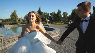 the bride and groom run near the old castle