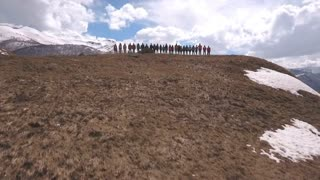 the group of travelers in the mountains raise their hands