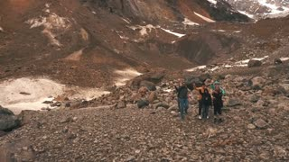 the group of travelers in the mountains waving to the camera