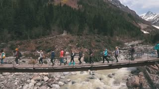 the group of travelers is on the bridge in the mountains