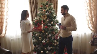 the husband gives Christmas gift to his wife