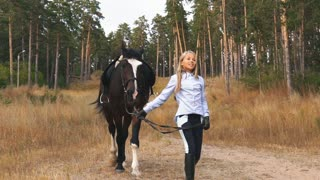 the little girl walks in autumn forest together with horse