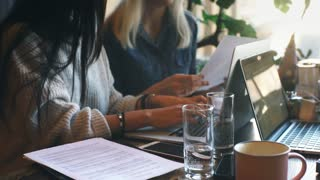 two businesswomen are actively working on a laptop in a cafe and discussing the work