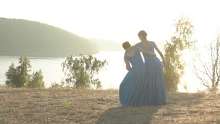two girls make a dance movement at sunset