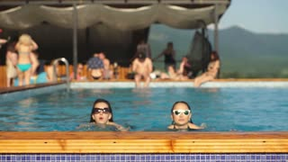 two women young women having fun in the pool