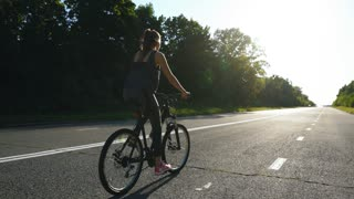 woman cycling alone riding bike at countryside, spending her active summer weekend