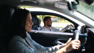 young attractive handsome man driving car and talking with woman