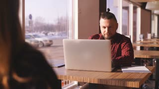 Young bearded businessman sits in cafe at table. On table laptop. Man is working, studying. Online education, marketing, training