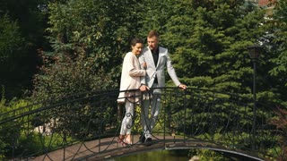 young beautiful couple walking in the Park and stands on the bridge