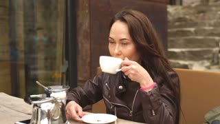 young beautiful woman drinking coffee in cafe on the street