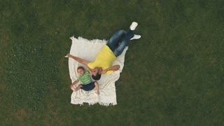 Young boy play with father on lawn, aerial shooting