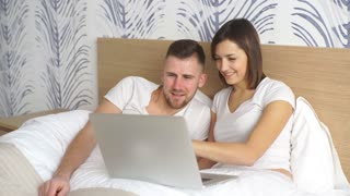 Young couple with laptop watching movie in bed