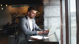 young handsome attractive bearded businessman sitting at the table in a suit and typing on a laptop with mobile near