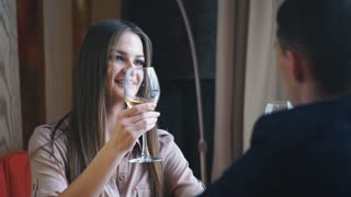Young happy couple romantic date drink glass of white wine at restaurant, celebrating valentine day
