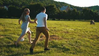young man and woman holding hands running through grass field