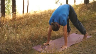 Young man practicing yoga ln the wood. Upward facing dog