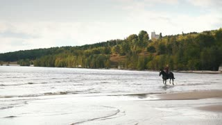 young pretty girl riding horse in river water