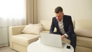 Young successful handsome man working with computer in a hotel room