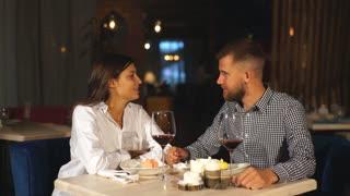 Young woman is feeding his man modern restaurant