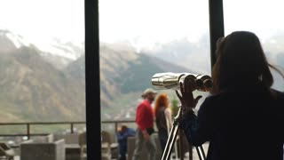 young woman looking through a telescope at the mountains