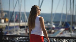 woman at the pier near yacht on the background of blue sky, selective focus