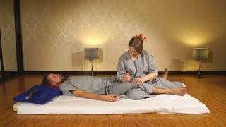 woman making thai massage to a man