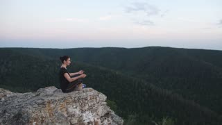 Yoga at summit with aerial view of the mountain range and peak