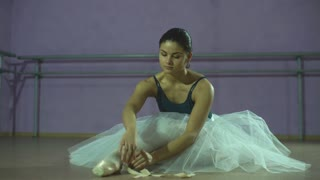 Young ballerina wears her pointe shoes