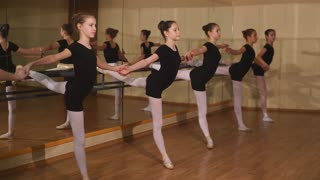 Young ballet dancers stands near the ballet barre at the ballet hall