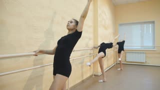 Young ballet dancers stands near the ballet barre