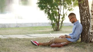 Young bearded man is sitting on green grass under the tree on the garden and working in his laptop