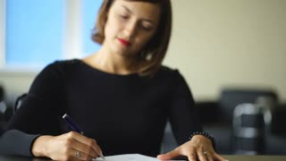 Young business woman signing contract