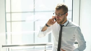 young businessman talking on the phone in the lobby of the office
