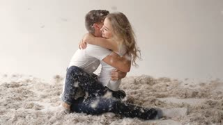 Young couple fighting pillows in the photostudio, on white background