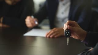 young couple is signing the sales contract and gets the key for the new car