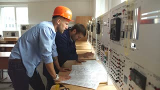 young engineer taking notes at control room in factory