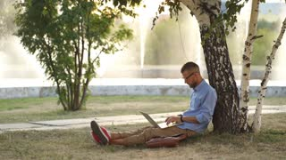 Young man using laptop in the park on a summers day