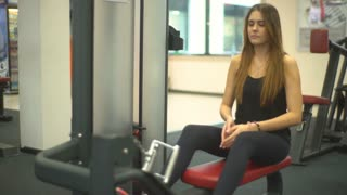 young pretty girl doing exercise on a simulator at the back muscles