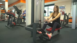 young pretty girl doing exercise on a simulator