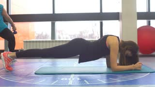 Young woman doing core exercise on fitness mat in the gym