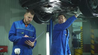 Young workshop employees working together underneath a lifted car