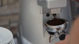 A shiny silver espresso machine makes coffee