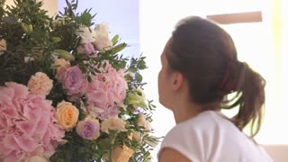 a woman's hands fixing the flowers in the bouquet. a florist creates a bouquet of hydrangeas, roses and orchids for festive decoration wedding,
