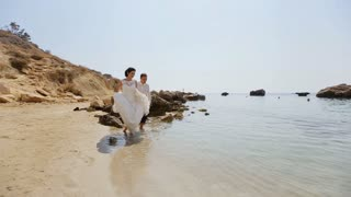 adult male groom and female bride running barefoot on beach