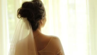 Beautiful brunette bride standing near the window