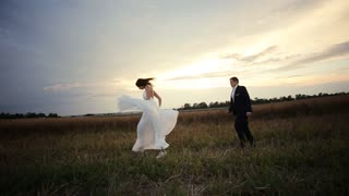 Beautifull couple running at the wheat field