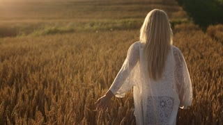 Beauty girl on yellow wheat field over sunset sky