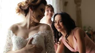 Best friend helps to pretty bride to wear a wedding dress