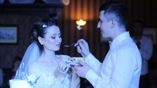 Bride and groom eating wedding cake